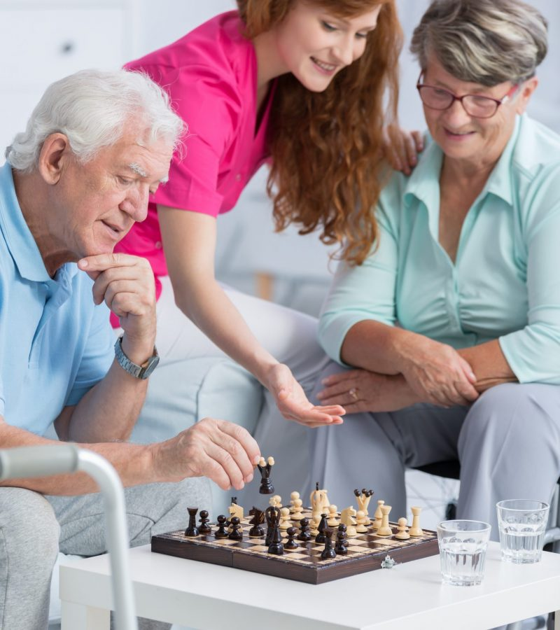 Elderly couple playing chess in nursing home and young caregiver helping them